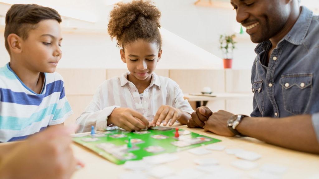 Família a jogar jogos de tabuleiro em casa